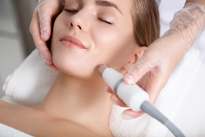 Close up of beautician hand making ultrasound facial procedure by special equipment. Her closed eyes with slight smile